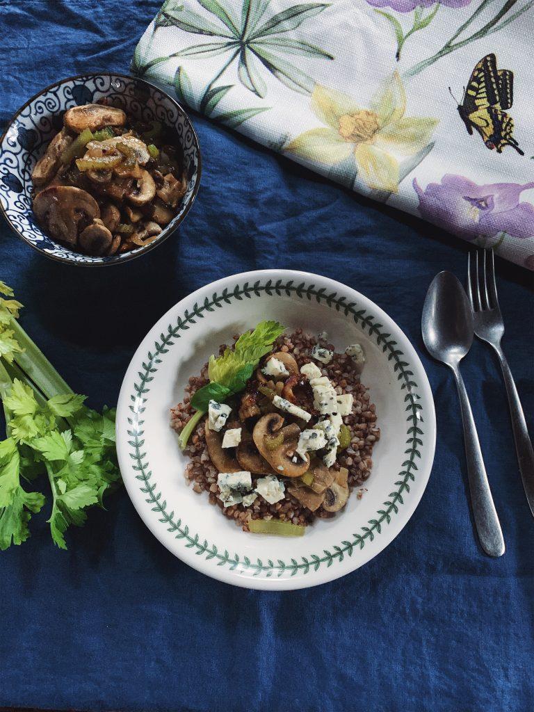 Grikiai su atskirai keptuvėje pakeptais svogūnais, salierais, grybais, gardinti sūriu su mėlynuoju pelėsiu